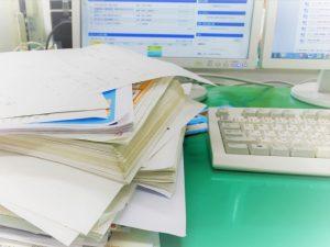 散らかった書類とパソコン